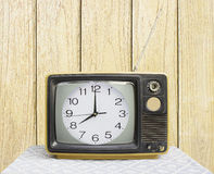 Clock on Vintage TV wood background Royalty Free Stock Image