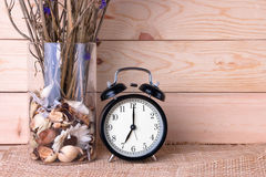 Clock with violet flower on wood background. Alarm Clock with violet flower on wood background stock images