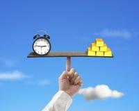 Clock vs gold balance on finger seesaw Stock Photo