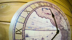 The clock on the wall. Timelapse. Analog Clock with the image of the world map hanging on the wall and work. Minute and hour hands run along the rim of the dial stock footage