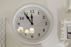 The clock on the wall is white. Eleven hours and fifty-five minu. Tes. Interior Royalty Free Stock Photo