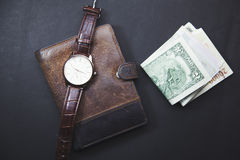 Clock on the wallet and money. Classic Watches, money on brown wallet Royalty Free Stock Image