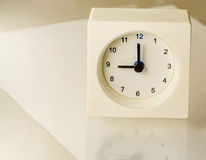 Clock. White clock display time as 9.00 oclock put on glass table stock photo