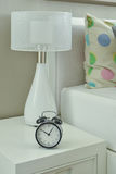 Clock and white lamp on bedside table in living room. Interior Royalty Free Stock Photos