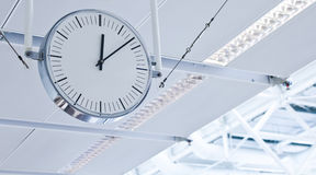 Clock. White clock with lines instead of numbers hanging from a ceiling at the airport Royalty Free Stock Photo