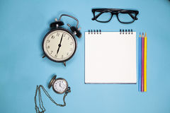 Clock, white notebook on springs, glasses and colored pencils on a blue background Royalty Free Stock Image