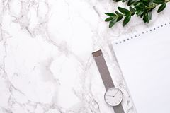 Clock , white notepad and greens on a marble background royalty free stock photo