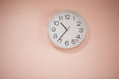 Clock white on a pink background. Stock Photos