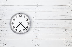 Clock on a white wooden wall Royalty Free Stock Image