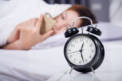 Clock with woman using her smartphone on bed. In the bedroom Stock Photo