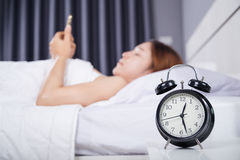 Clock with woman using her smartphone on bed. In the bedroom Stock Photos