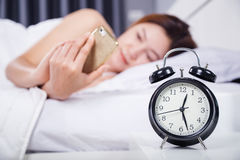 Clock with woman using her smartphone on bed. In the bedroom Stock Image