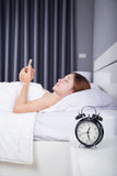 Clock with woman using her smartphone on bed. In the bedroom Royalty Free Stock Photos