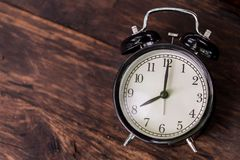 Clock on wood background time at 8 o`clock. Retro vintage style top view with space stock photos