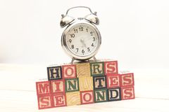 Clock with wood cubes on wooden table words hours,minutes,seconds cool Royalty Free Stock Photography