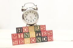 Clock with wood cubes on wooden table words hours,minutes,seconds cool Royalty Free Stock Image