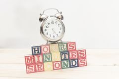 Clock with wood cubes on wooden table words hours,minutes,seconds cool Stock Photos