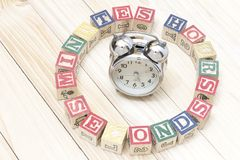 Clock with wood cubes on wooden table words hours,minutes,seconds cool. Clock with wood cubes on wooden table words hours,minutes,seconds Royalty Free Stock Image