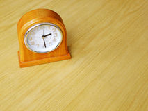 Clock on wood table Royalty Free Stock Photos