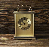 Clock on a wooden background. Vintage clock on the brown wood texture Royalty Free Stock Photo