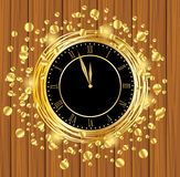 Clock on a wooden background with gold spangles Royalty Free Stock Image