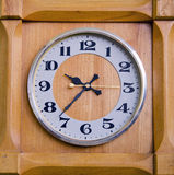 Clock in wooden box showing twentyseven past nine. Stock Images