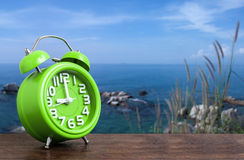 Clock on Wooden Floor with Blue Sky and Hillock Background stock images