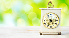 Clock on a wooden table Stock Images