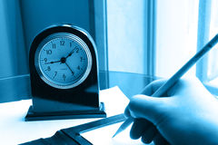 Clock and writing hand on note Royalty Free Stock Photography