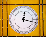 Clock on yellow wall Stock Photos