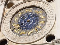 Clock with zodiacal signs enamelled in gold and blue constellations illuminated by the sun. Clock placed in Piazza San Marco, lit by the midday sun royalty free stock photos