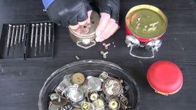 Clockmaker handen die oude alarm-klok herstellen stock videobeelden