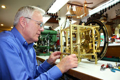 Clockmaker working on a clock. A senior man working on a clock assembly stock image