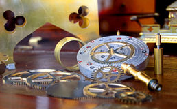 Clockmakers cogs. Photo of clockmakers cogs and precision tools laid out on a mahogany bench Royalty Free Stock Image