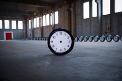 Clocks with red door. A black clock with no hands stands in the foreground, with 50 clocks behind, settled in a row pointing to a red door placed in the royalty free stock images
