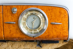 Clocks retro car. Old refurbished car. Wood trim, dashboard fragment - round clock with arrows and numbers. Chrome-plated metal parts of the car interior trim Royalty Free Stock Photos