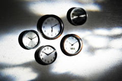Clocks on shadowy wall Stock Photography