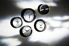 Clocks on shadowy wall Stock Photography