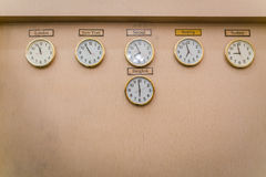 Clocks shows different time zones on old wall . Royalty Free Stock Photo