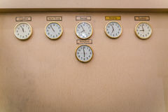 Clocks shows different time zones on old wall . Stock Photos