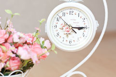 Clocks on stand on floor with flowers. White Clocks with flowers on stand stock images