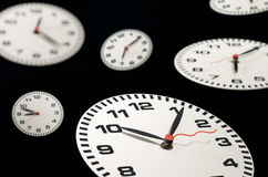 Clocks & times. Lots of clocks floating on black background Royalty Free Stock Images