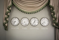 Clocks on a wall with time zone of different country Stock Photos