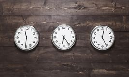 Three wall clocks on different time zones. Clocks on a wooden background with time zone of different country. London, New York, Paris royalty free stock images