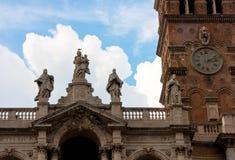 CLOCKTOWER和雕象在大教堂屋顶在罗马 免版税库存图片