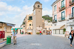 The clocktower. CAPRI, ITALY - OCTOBER 3, 2012: The old clocktower on the Piazza Umberto I surrounded by luxury stores and restaurants, on October 3 in Capri Royalty Free Stock Photos