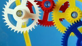 Clockwork spin. Working multicolor plastic toy cog of clockwork on blue screen stock video