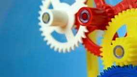 Clockwork spin. Working multicolor plastic toy cog of clockwork on blue screen stock video footage