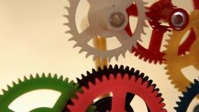Clockwork spin. Working multicolor plastic toy cog of clockwork on gradient dark screen stock video footage