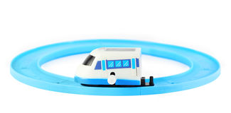 Clockwork toy white train on railroad. Bright clockwork toy white train with blue windows on railroad on white background Stock Images